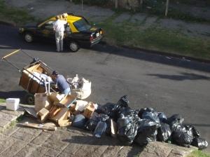 Cartonero madrugador frente a la Facultad de Derecho de la UBA, en su tarea de clasificador, cargado y traslado de cartones, botellas, metales y papel.