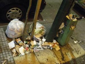 Si no se retiran los residuos con mayor frecuencia, rebasan y la gente continúa acumulando alrededor, ensuciando la vereda. Centro de Adrogué.