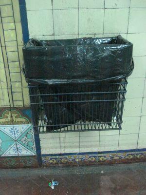 Subterráneo. Papelero al paso con bolsa de residuos.