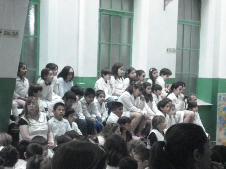 Nutridos grupos de alumnos atendiendo y festejando el aniversario de su escuela.